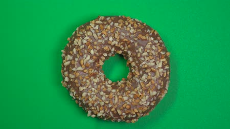 жареный : Tasty and fresh sprinkled donut close-up macro shot spinning on a green background. Стоковые видеозаписи