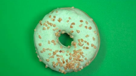 zasklený : Tasty and fresh sprinkled donut close-up macro shot spinning on a green background. Dostupné videozáznamy