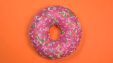 plain : Tasty and fresh sprinkled donut close-up macro shot spinning on a orange background. Stock Footage