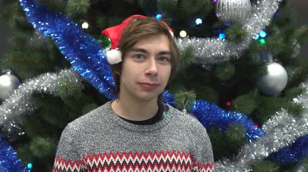 Санта : Portrait of Handsome Young Man in Santa Hat Looking at the Camera on Christmas Tree Background.