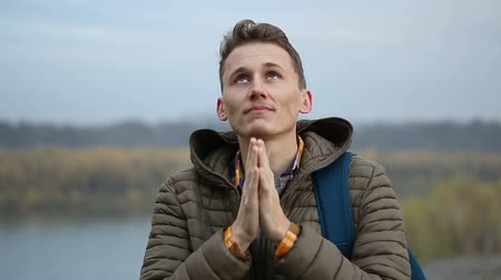 Handsome man praying outdoor, close-up portrait of guy in morning nature