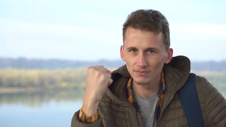 Portrait of an angry white man shaking his fist looking to the camera aggressively outdoor Стоковые видеозаписи