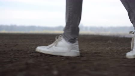 kotník : Shot of men feets in sneakers walking on ground road. Nature Environment