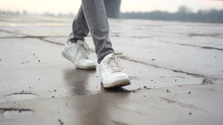 tiled floor : Steps in white sneakers on a wet tiled road Stock Footage