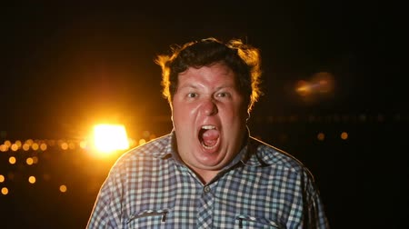pánik : Fat raged man standing and screaming in panic or terror at night outdoor, portrait