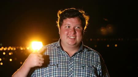 Man standing and showing thumb up at night outdoor, portrait