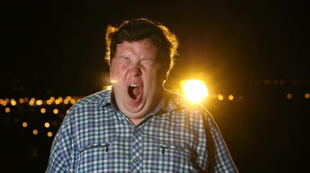 Bored man standing and yawning at night outdoor, portrait
