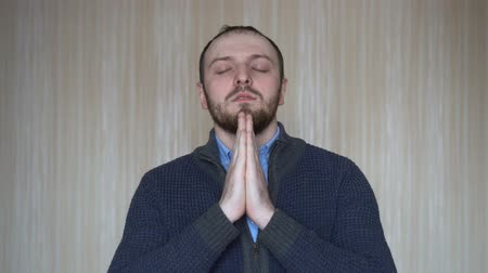 угождать : Portrait of hopeful young bearded man keeps hands together in praying gesture