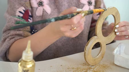 acht : Making wooden decorations from wooden number eight and golden glitter. Workplace