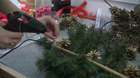 çelenk : Woman decorating handmade christmas branch with pine cones and shine beads Stok Video