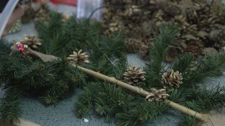 çelenk : Woman decorating handmade christmas branch with shine beads and pine cones Stok Video