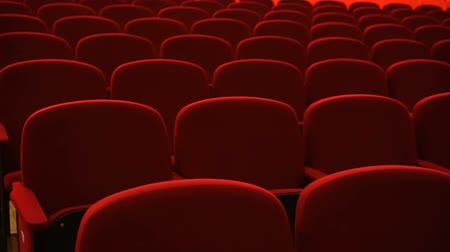 初演 : Rows of empty red velvet seats inside a theater or opera