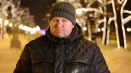 hat : Portrait of handsome man saying no by shaking head outdoors during cold winter night Stock mozgókép