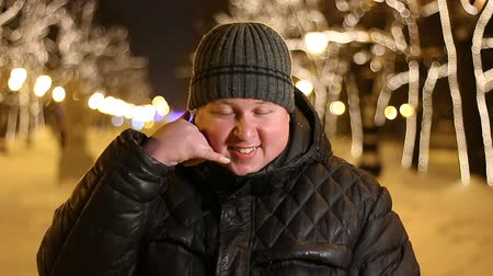 contacteer ons : Portrait of happy man making a gesture call me with his fingers outdoors during cold winter night