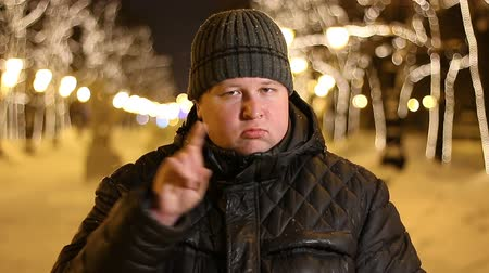 sem camisa : Portrait of handsome man emotions of discontent, showing a sign with his finger outdoors during cold winter night Stock Footage