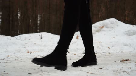ślady stóp : Close-up of womans feet in boots walking on the snow desert. Wideo