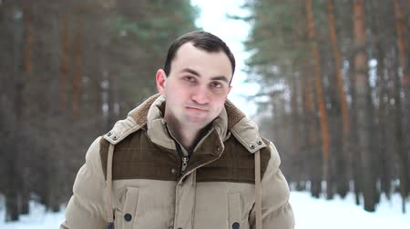 rejeitar : Portrait of man in jacket rejecting something by nodding his head. Man stands in winter forest