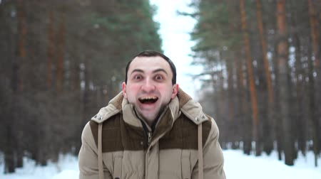 восхищенный : Portrait of amazed man in a jacket is showing wow emotion at camera. Man stands in winter forest