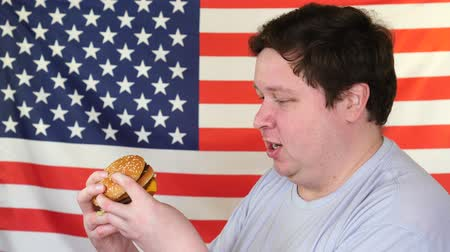 plezant : Man with a hamburger with an American flag background. Big guy wants fast food
