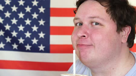 close cropped : Close-up of a man drinking a cocktail from straw in front of the American Flag Stock Footage