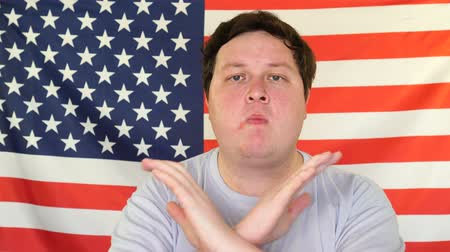 odmítnutí : Man with crossed hands showing stop gesture on the Background of an USA Flag Dostupné videozáznamy
