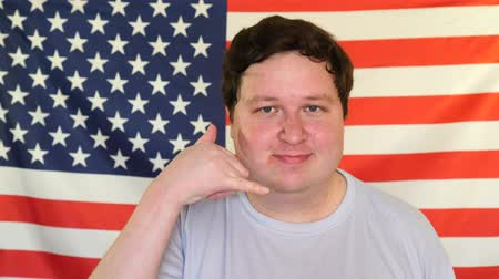 contacteer ons : Young man showing call me gesture on the background of an USA flag