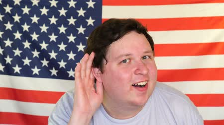 front national : Young man eavesdropping on the background of an USA flag Stock Footage