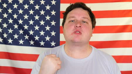 pięśc : Young big man threateningly showing his fist. Portrait on the background of an USA flag Wideo