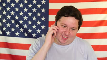 front national : Young fat man talking on the phone on the background of an USA flag