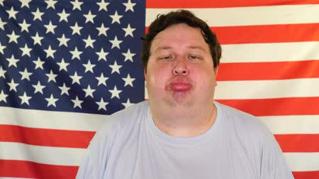 galhofeiro : Portrait of fat man making funny faces on the background of an USA flag