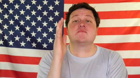 emelt : Young man raising hand on the background of an USA flag