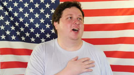 hymn : Man Singing the National American Anthem on the Background of an USA Flag Stock Footage