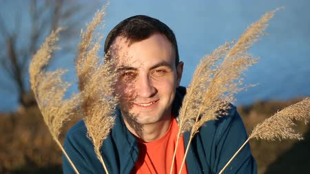 kamış : Portrait of handsome smiling man with dry grass, reeds outdoor