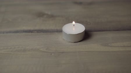 symbolismus : One burning candle on a wooden table