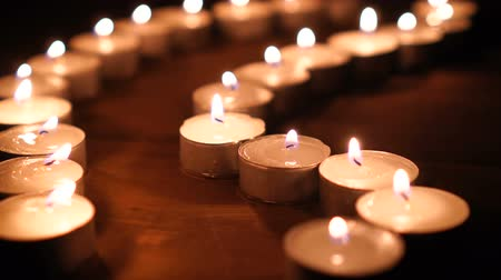 profundidade de campo rasa : Many candle flames glowing in the dark, create a spiritual atmosphere Stock Footage