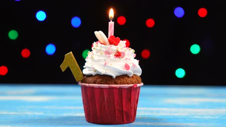 çırpılmış : Delicious birthday cupcake with burning candle and number 1 on multicolored blurred lights background Stok Video