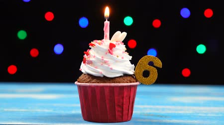 seis : Delicious birthday cupcake with burning candle and number 6 on multicolored blurred lights background