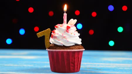 sete : Delicious birthday cupcake with burning candle and number 7 on multicolored blurred lights background