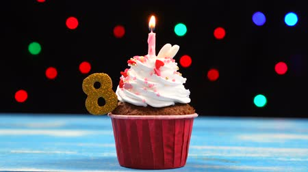eight : Delicious birthday cupcake with burning candle and number 8 on multicolored blurred lights background Stock Footage