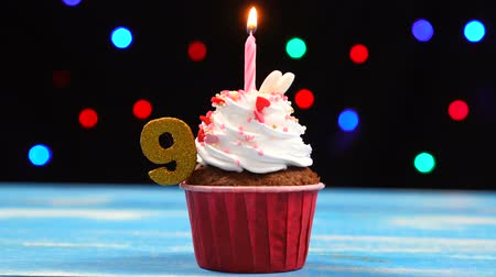 devět : Delicious birthday cupcake with burning candle and number 9 on multicolored blurred lights background Dostupné videozáznamy