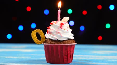 окропляет : Delicious birthday cupcake with burning candle and number 0 on multicolored blurred lights background