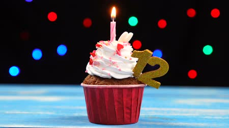 buttercream : Delicious birthday cupcake with burning candle and number 12 on multicolored blurred lights background Stock Footage