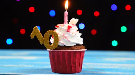 šlehačka : Delicious birthday cupcake with burning candle and number 10 on multicolored blurred lights background