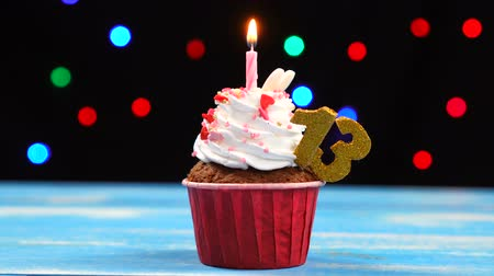 gênero alimentício : Delicious birthday cupcake with burning candle and number 13 on multicolored blurred lights background Stock Footage