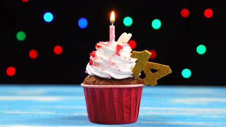 šlehačka : Delicious birthday cupcake with burning candle and number 14 on multicolored blurred lights background Dostupné videozáznamy