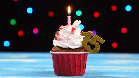 šlehačka : Delicious birthday cupcake with burning candle and number 15 on multicolored blurred lights background