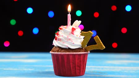 seventeen : Delicious birthday cupcake with burning candle and number 17 on multicolored blurred lights background