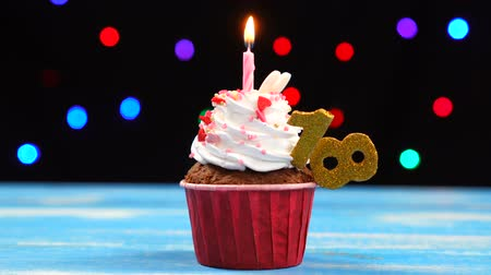 osiemnastka : Delicious birthday cupcake with burning candle and number 18 on multicolored blurred lights background