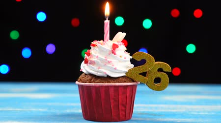 gênero alimentício : Delicious birthday cupcake with burning candle and number 26 on multicolored blurred lights background
