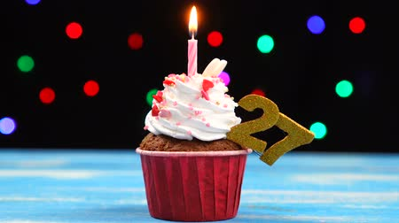 sete : Delicious birthday cupcake with burning candle and number 27 on multicolored blurred lights background